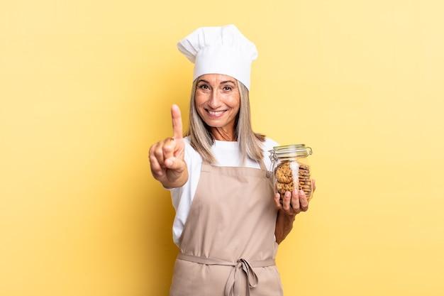 Kobieta szefowa kuchni w średnim wieku, uśmiechnięta dumnie i pewnie, triumfalnie wykonująca pozę numer jeden, czując się jak liderka z ciasteczkami