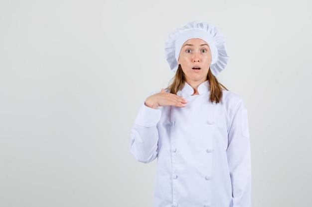"""Kobieta szefowa pokazująca """"mnie""""? gest w białym mundurze i wyglądający na zdezorientowanego"""