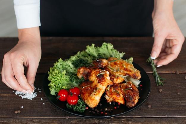 Kobieta szefowa serwująca pikantne skrzydełka z kurczaka