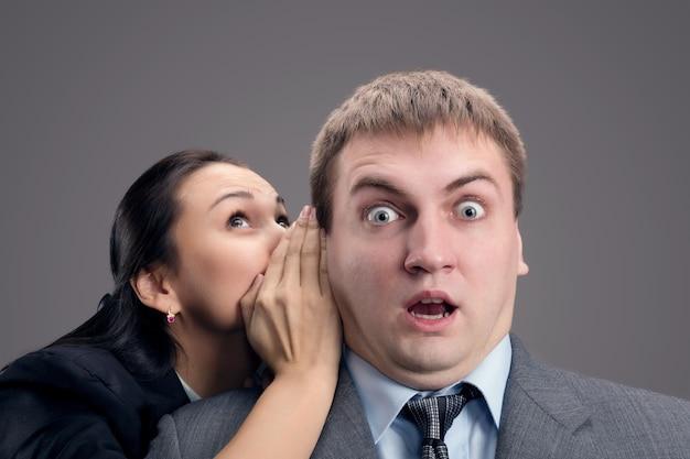Kobieta szepcząca do mężczyzny