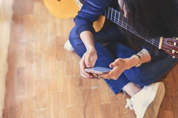Kobieta szkolenia gitara z wykorzystaniem inteligentnego telefonu komórkowego.