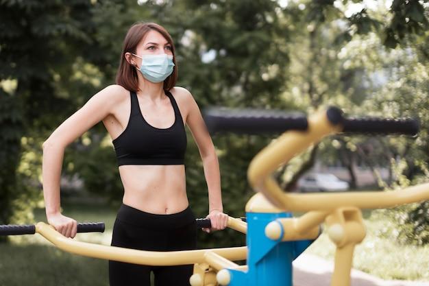 Kobieta szkolenia na następne wydarzenie sportowe podczas noszenia maski medycznej