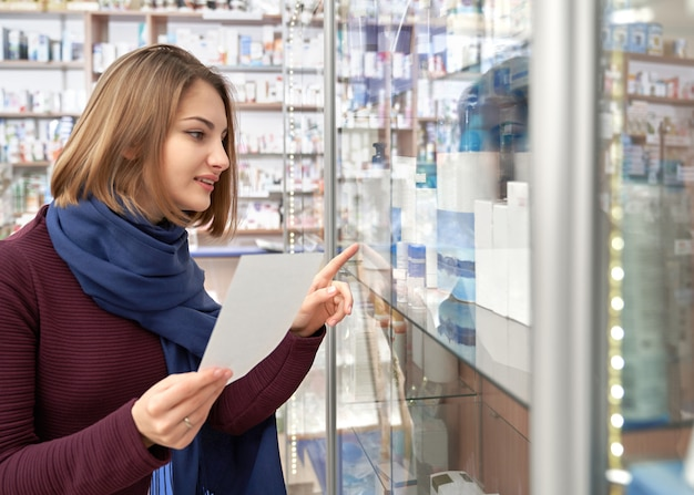 Kobieta szuka leków na receptę w drogerii.