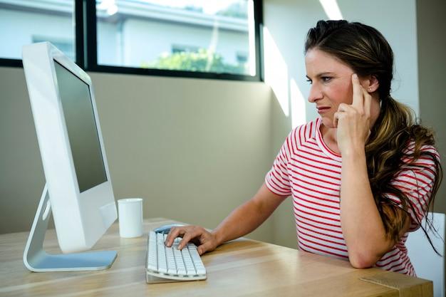 Kobieta szuka niezadowolonego, siedząc przy biurku na swoim komputerze