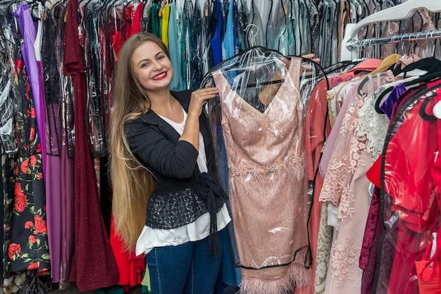 Kobieta szuka sukni wieczorowej w sklepie