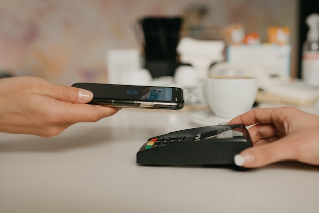 Kobieta szykuje się do zapłaty za swoje latte smartfonem dzięki bezdotykowej technologii nfc w kawiarni. baristka trzyma terminal za płacenie klientowi w kawiarni.