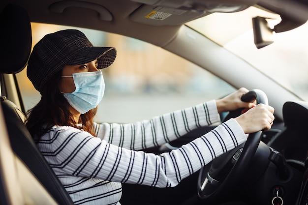 Kobieta taksówkarz jedzie w sterylnej masce medycznej podczas kwarantanny pandemicznej koronawirusa