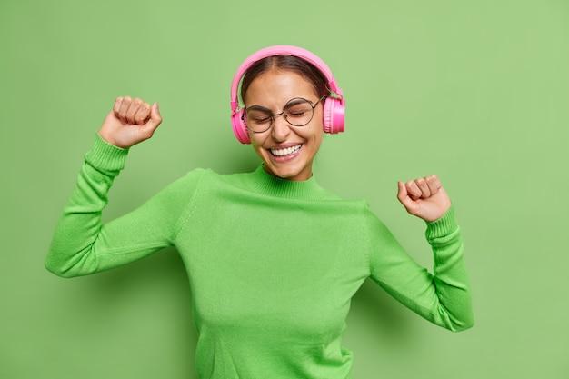 Kobieta tańczy beztrosko podnosi ręce jest zadowolona łapie każdy kawałek muzyki słucha muzyki w bezprzewodowych słuchawkach nosi okulary z golfem na zielono