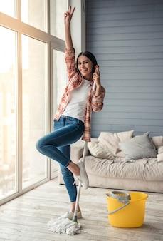 Kobieta tańczy i uśmiecha się podczas czyszczenia podłogi w domu.