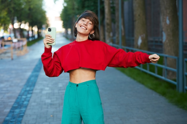 Kobieta tańczy na ulicy z telefonem, śliczna tysiącletnia kobieta w czerwonym stylowym swetrze o tańcu smartfona w nowoczesnym mieście