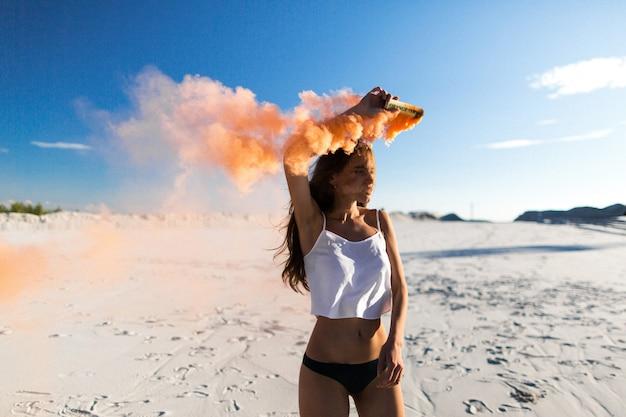Kobieta tańczy pomarańczowy dym na białej plaży pod błękitnym niebem
