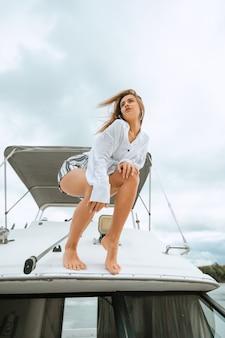 Kobieta tańczy stojąc na nosie jachtu w słoneczny letni dzień, bryza rozwija włosy. wspólna zabawa i cieszenie się słońcem podczas żeglowania po morzu. koncepcja podróży i żeglarstwa.