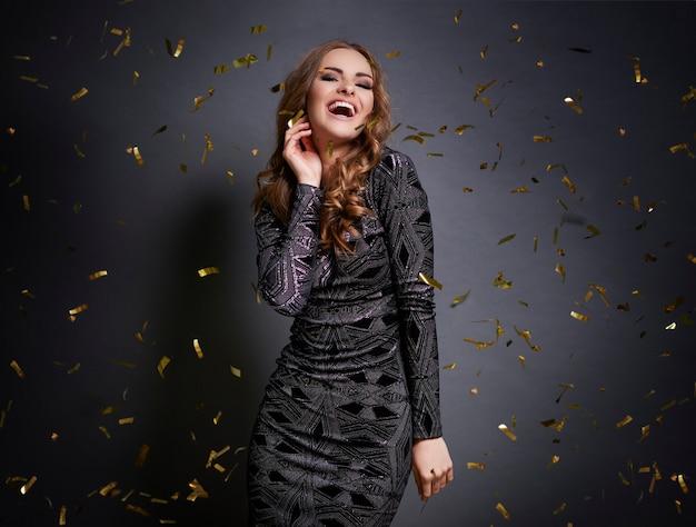 Kobieta tańczy z spadającymi konfetti