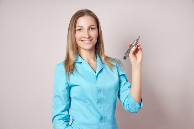 Kobieta tatuażysta makijaż permanentny z maszyną do tatuażu w ręku