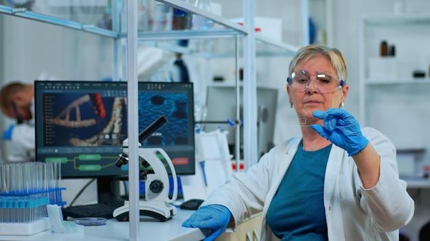 Kobieta technik laboratoryjny patrząc na próbki wirusa w nowocześnie wyposażonym laboratorium. starszy naukowiec pracujący z różnymi badaniami tkanek i krwi bakterii, koncepcja badań farmaceutycznych nad antybiotykami