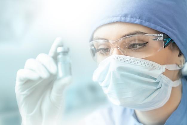 Kobieta technik laboratoryjny z ampułką szczepionki wirusowej.