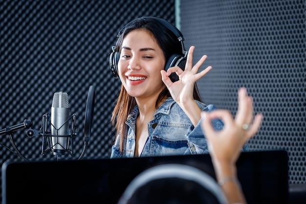 Kobieta technik studyjny monitora komputerowego oprogramowania do nagrywania na pierwszym planie młodej wokalistki azjatyckiej kobiety noszącej słuchawki nagrywająca piosenkę przed mikrofonem w profesjonalnym studiu