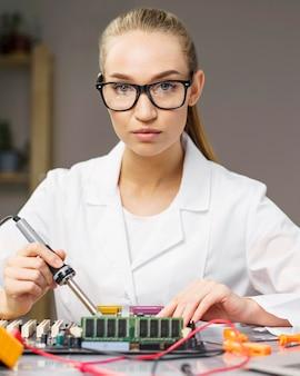 Kobieta technik z płytką elektroniki i lutownicą