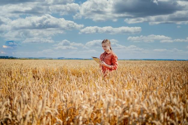 Kobieta technolog kaukaski agronom z komputera typu tablet w polu pszenicy