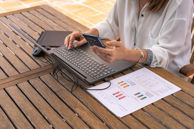 Kobieta telepraca z domu w ogrodzie z laptopem i telefonem komórkowym.