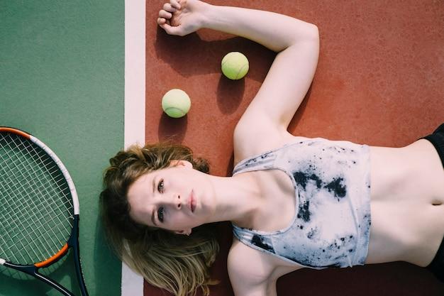 Kobieta tenisista le ?? cego na ziemi i patrz? c na niebo