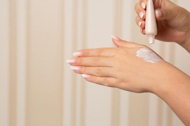 Kobieta testująca płynny rozświetlacz na dłoni. miejsce na tekst