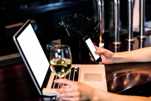Kobieta texting i używa laptop z winem w barze