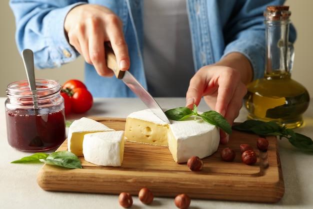 Kobieta tnie camembert na deska do krojenia, z bliska
