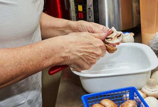 Kobieta tnie grzyby na drewnianej desce do krojenia. gotuje według przepisu w domu w kuchni