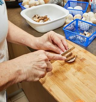 Kobieta tnie grzyby na drewnianej desce do krojenia. gotuje według przepisu w domu w kuchni.