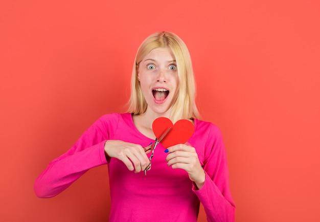 Kobieta tnie serce nożyczkami piękna dziewczyna tnie nożyczkami czerwone serce koncepcja łamania