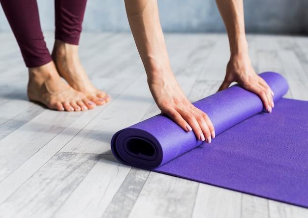 Kobieta toczenia jej matę do jogi