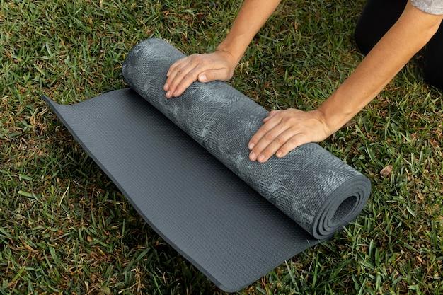 Kobieta toczenia mata do jogi na trawie