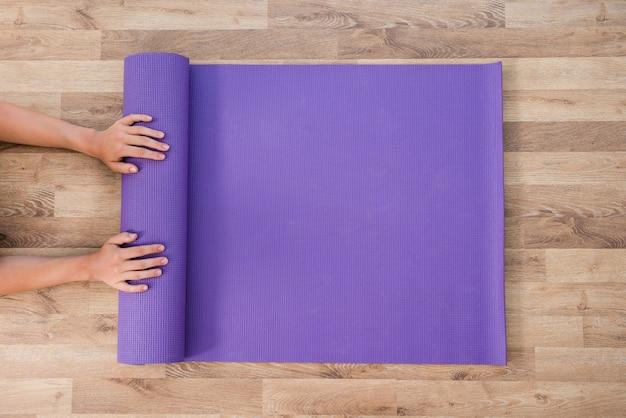 Kobieta toczenia matę do jogi