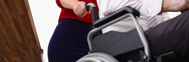 Kobieta toczy mężczyznę na wózku inwalidzkim w biurze