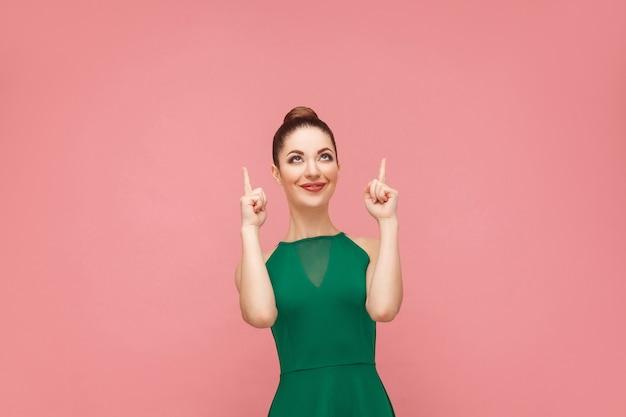 Kobieta toothy uśmiechając się i wskazując palcem w górę na miejsce. koncepcja ekspresji emocji i uczuć. strzał studio, na białym tle na różowym tle