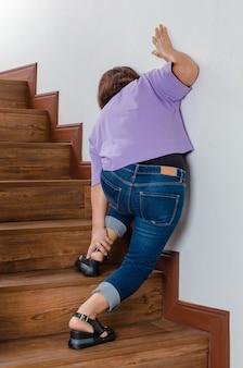 Kobieta traci kontrolę i nie może chodzić po schodach, zatrzymuje się i podtrzymuje nogi dla podparcia i odpoczywa z uczuciem mrowienia. pojęcie zespołu guillain-barre i choroby zdrętwiałych nóg lub efekt uboczny szczepionki.
