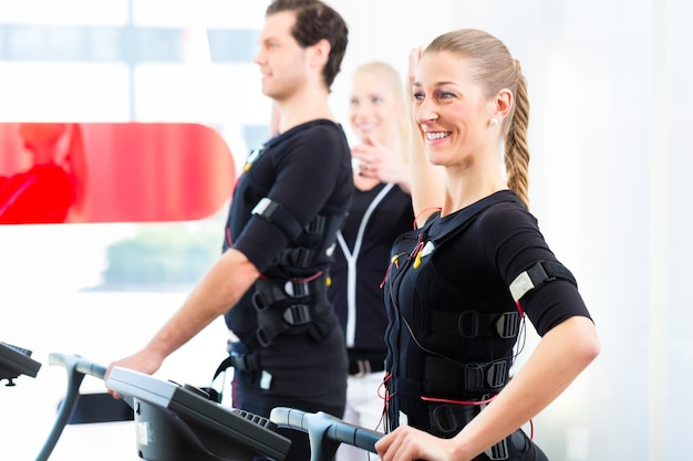 Kobieta trener dając mężczyznom i kobietom ćwiczenia stymulacji mięśni ems electro