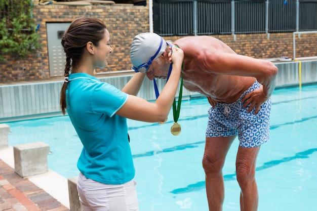 Kobieta trener dając złoty medal starszemu mężczyźnie przy basenie