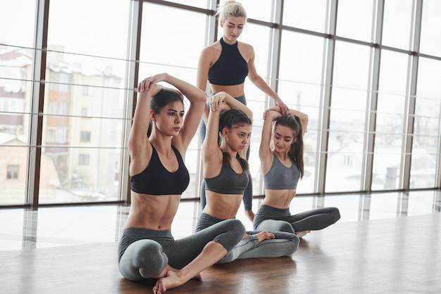 Kobieta trener nauki kobiet, jak do fitnessu. grupa sportowych dziewcząt w przestronnej siłowni z dużymi oknami ma trening