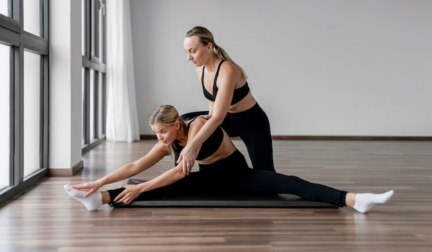 Kobieta trener osobisty pomaga jej klientowi z ćwiczeniami rozciągającymi
