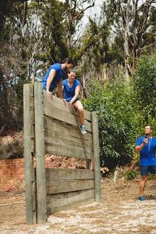 Kobieta trener pomaga człowiekowi wspiąć się na drewnianą ścianę