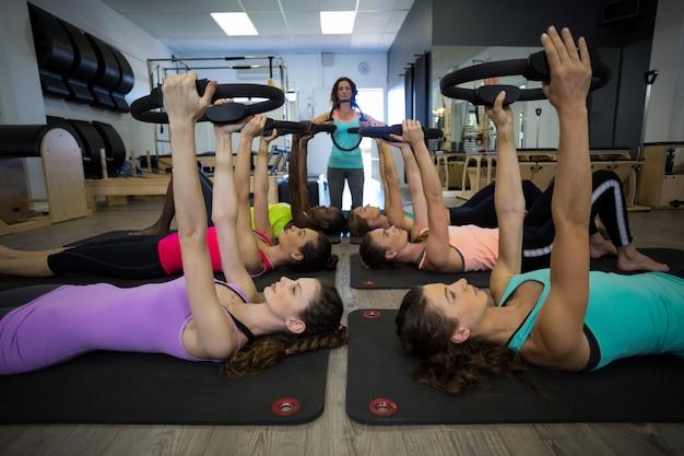 Kobieta trener pomaga grupie kobiet z ćwiczeniami na pierścieniu pilates