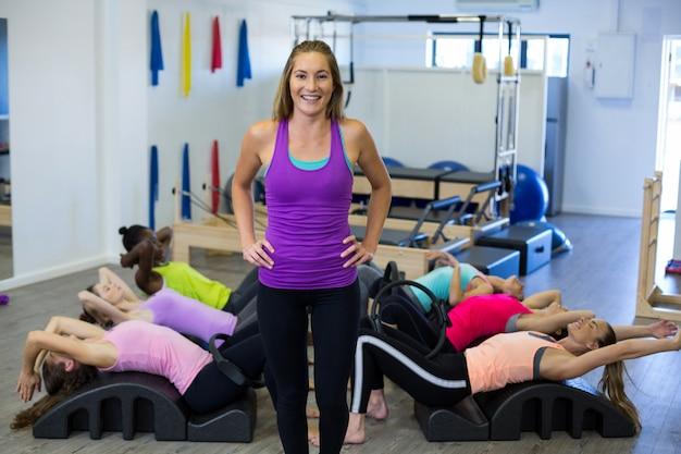 Kobieta trener pomaga grupie kobiet z ćwiczeniami rozciągającymi na lufie łuku
