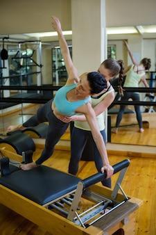 Kobieta trener pomaga kobiecie w ćwiczeniach rozciągających na reformatorze