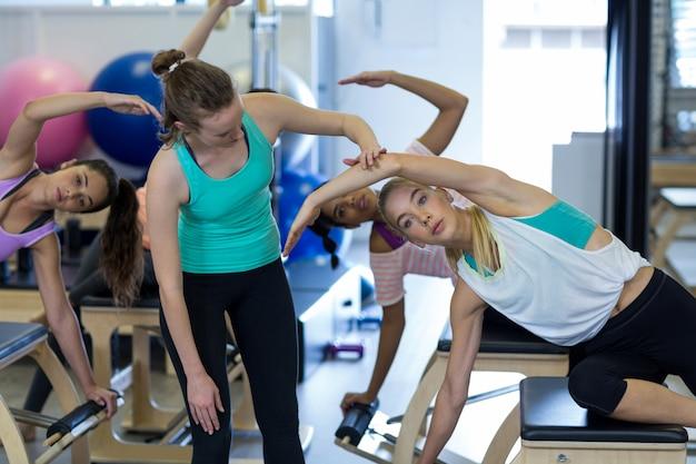 Kobieta trener pomaga kobiecie w ćwiczeniach