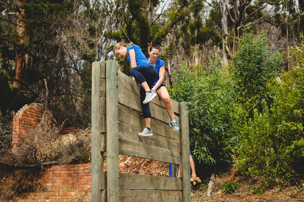 Kobieta trener pomaga kobiecie wspiąć się na drewnianą ścianę