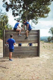 Kobieta trener pomaga sprawnemu człowiekowi wspiąć się na drewnianą ścianę podczas toru przeszkód