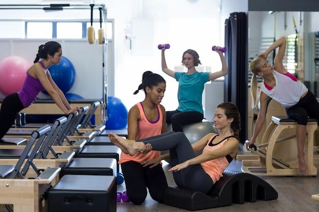 Kobieta trener pomagając kobiecie z ćwiczeń rozciągających na lufie łuku