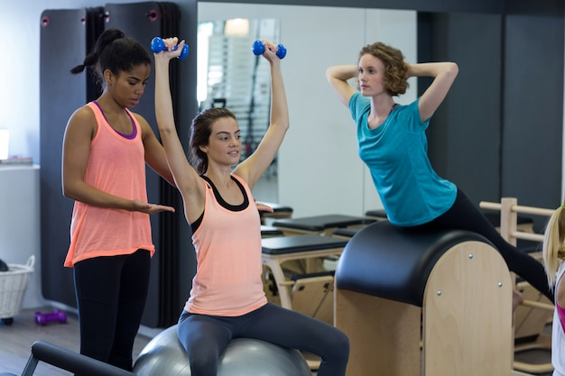 Kobieta trener pomagając kobiecie z ćwiczeń rozciągających na piłce fitness